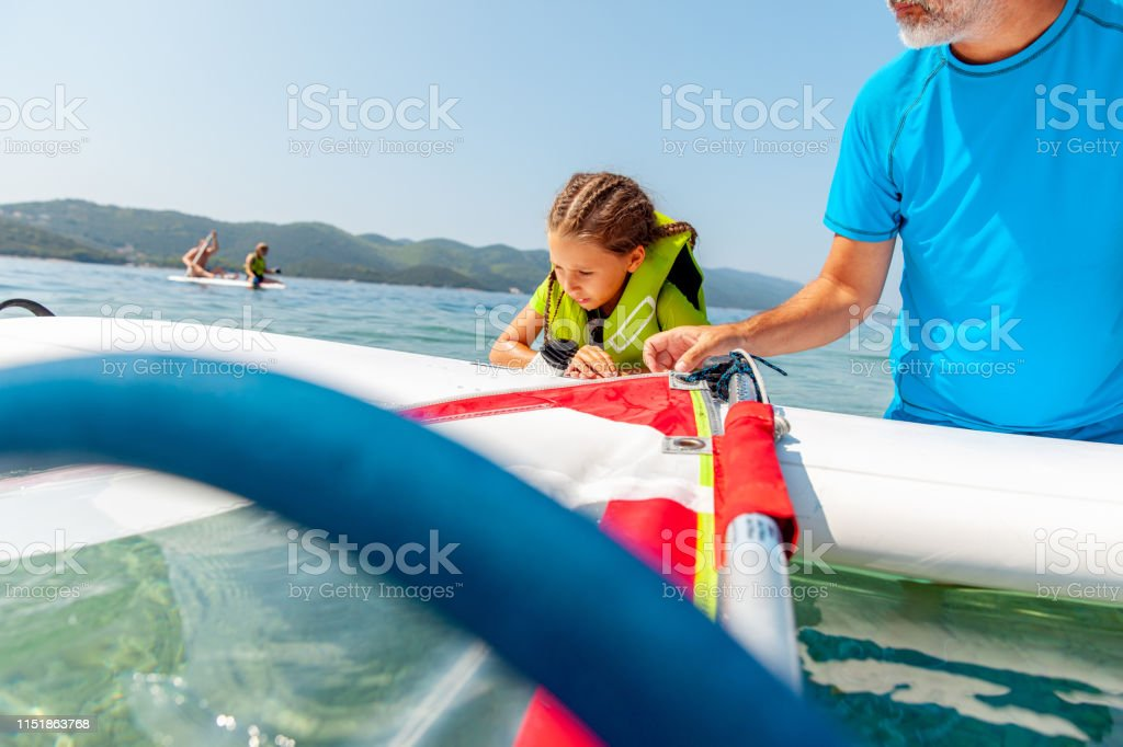 Little Girl Trying To Climb The Windsurf Board In The Water