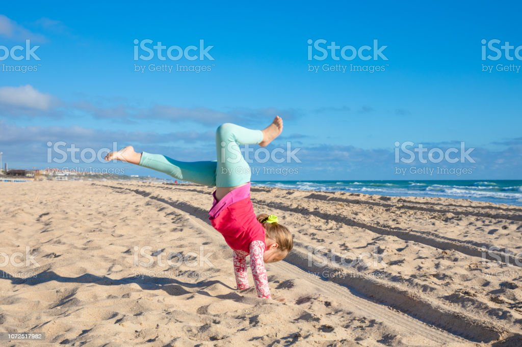 little girl trying to do handstand on sandy Beach La Barrosa stock photo