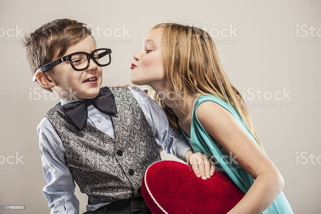 Little girl trying to kiss nerdy boy stock photo more pictures little girl trying to kiss nerdy boy royalty free stock photo altavistaventures Images