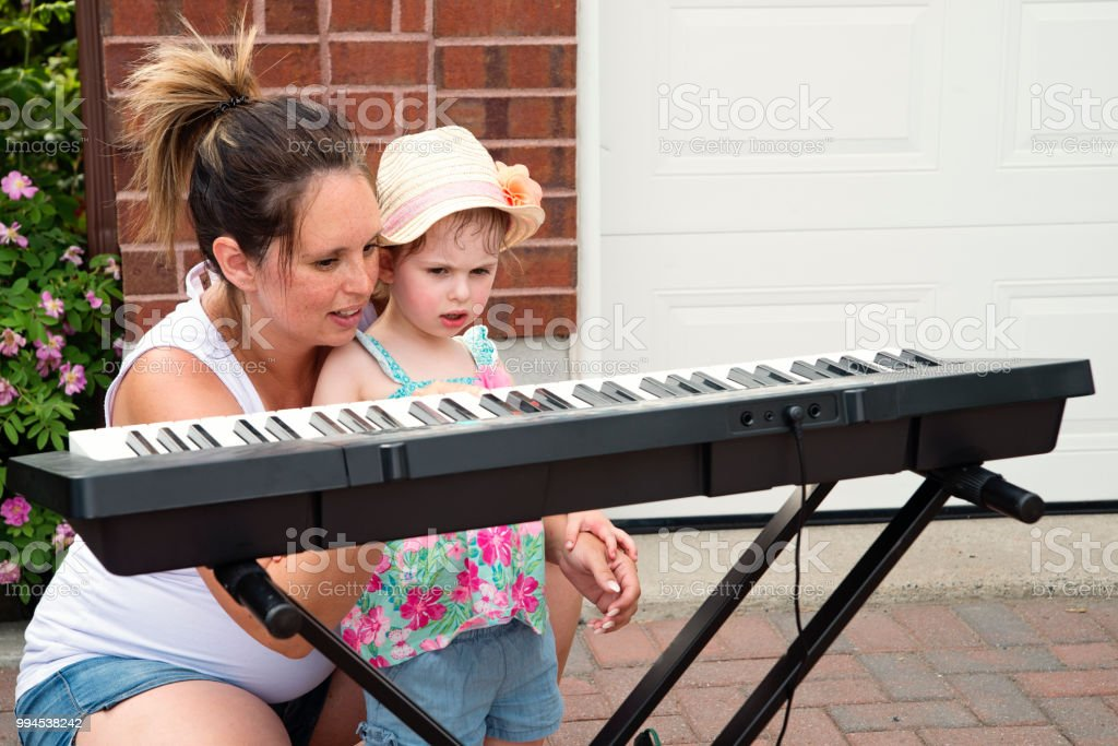 Little girl trying to play keyboard before show in family driveway. stock photo