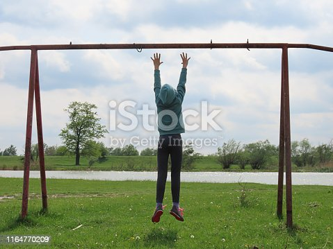 An Acrobatic Cute Teenage Girl with Long Hair, in Hooded Sweatshirt, is Having Fun On the River Bank. She is Jumping to Reach and to Hold Horizontal Bar in Outdoor Playground.
