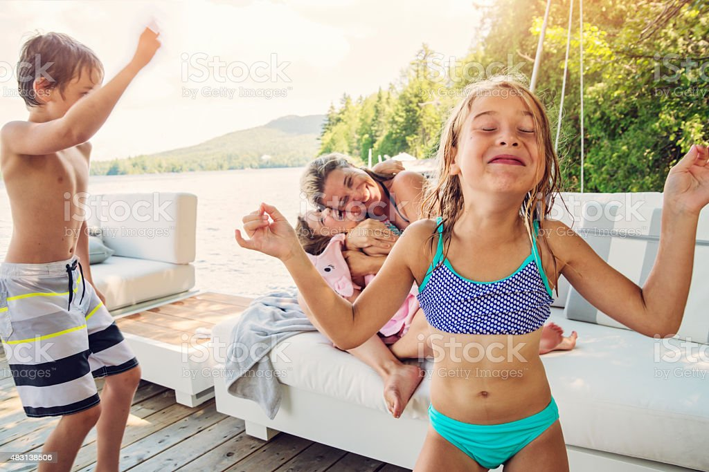 Little girl trying to stay zen while family goofing around. stock photo