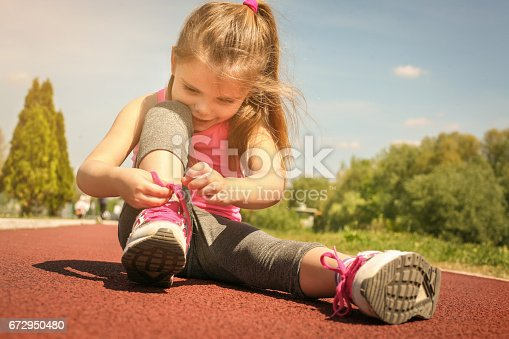 istock Little girl tying laces on sneakers. 672950480