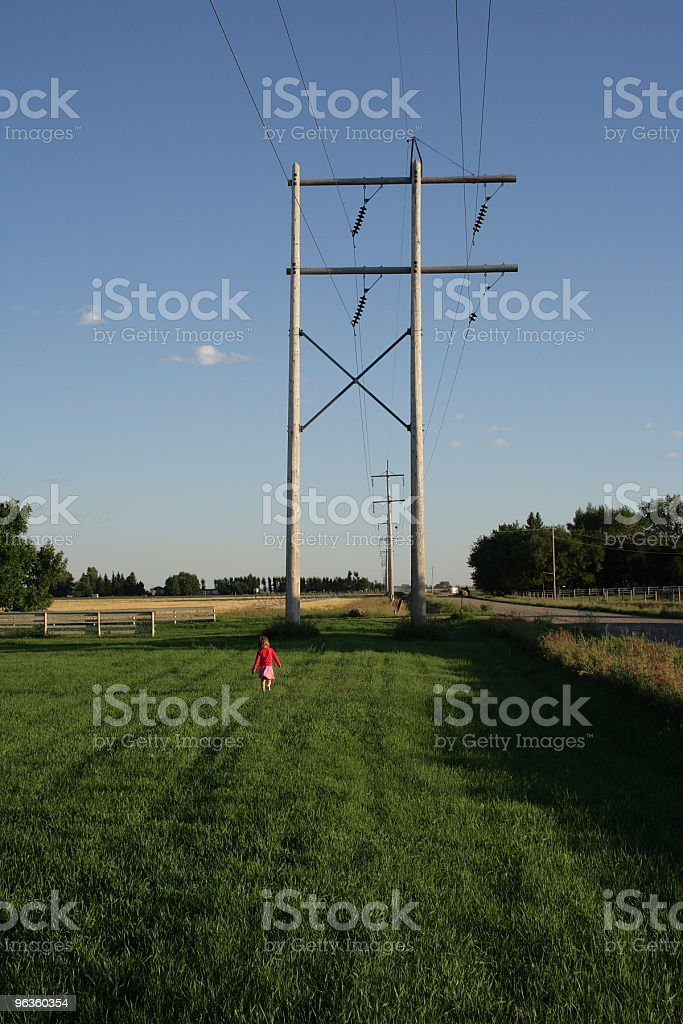 Little girl under large electric towers in field royalty-free stock photo