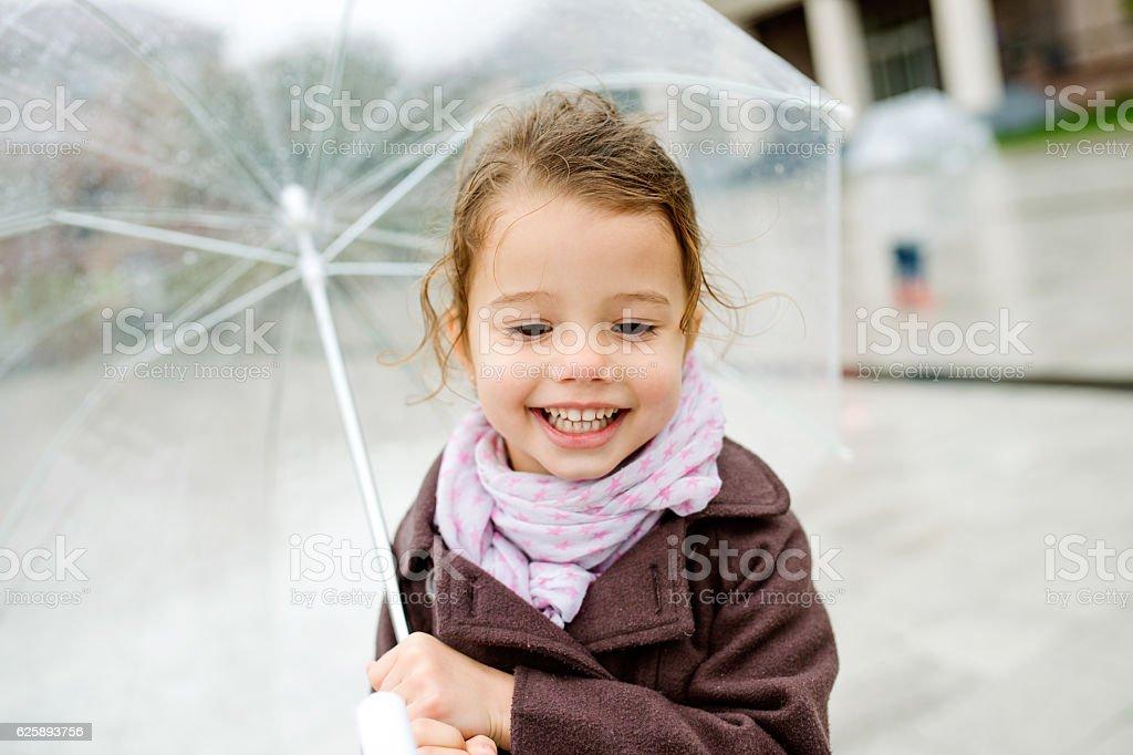 Little girl under the transparent umbrella outside, rainy day. stock photo