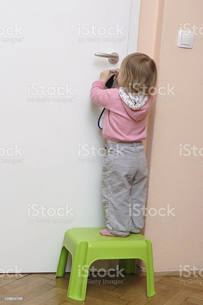 Little girl unlocking the door stock photo