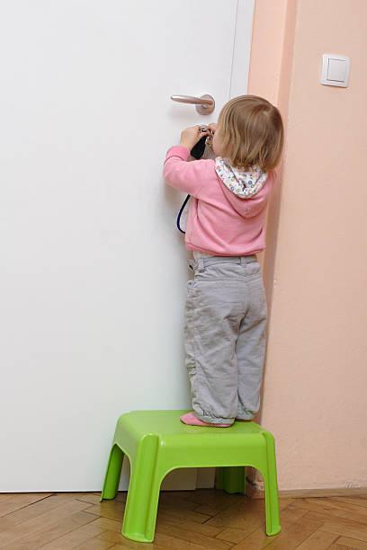 Little girl unlocking the door stock photo