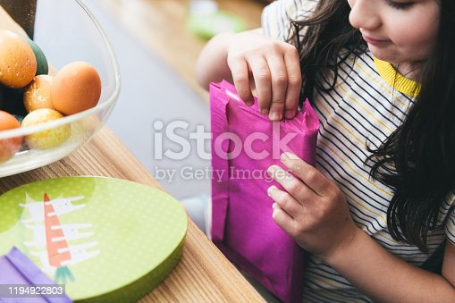 overhead view on little girl sitting on wooden table unwrapping pink   gift box