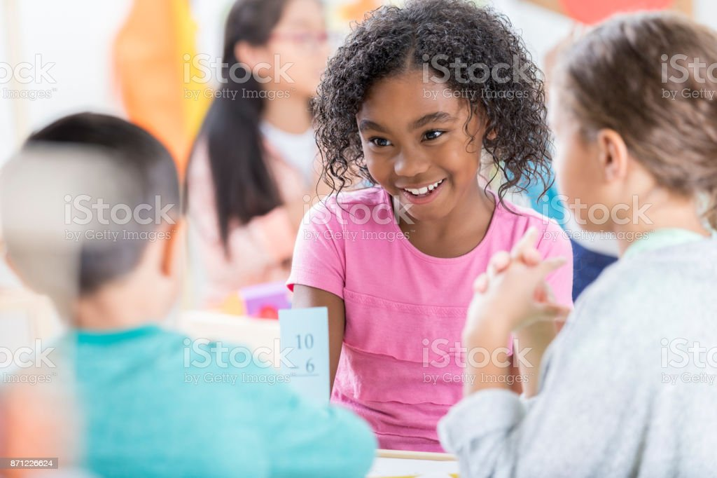 Little girl uses mathematics flash card to quiz friend stock photo
