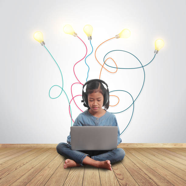 little girl using a laptop with creative light bulb ideas plugged in it, sitting on wall room with a hardwood wooden floor - genius stock photos and pictures