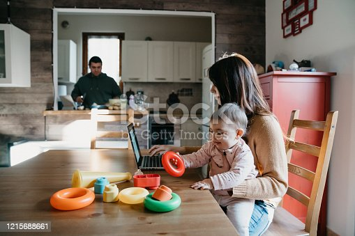 A little girl using a laptop with her mom while the dad is cooking in the kitchen. They are sitting at the table, the mother is holding her daughter. Family locked down during Coronavirus Covid-19 quarantine.