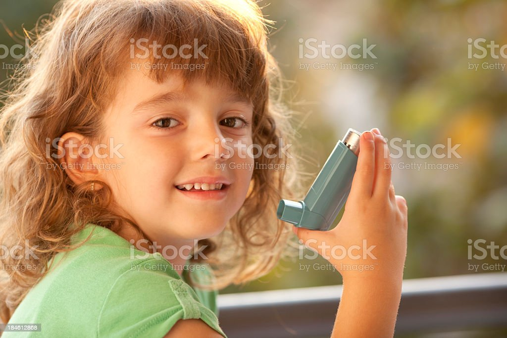Little Girl using Asthma Inhaler Outdoor stock photo