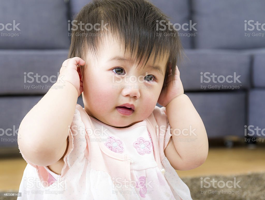 Little girl using hand to cover ear stock photo