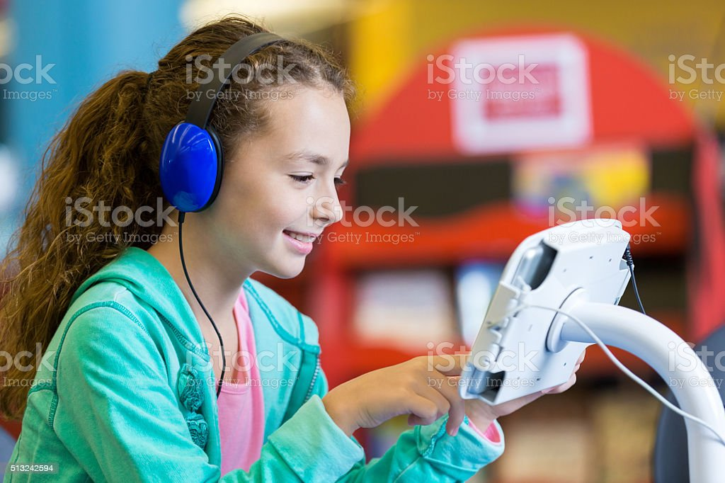 Little girl using headphones and digital tablet in modern library stock photo