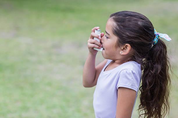 little girl using his inhaler - astmatisk bildbanksfoton och bilder