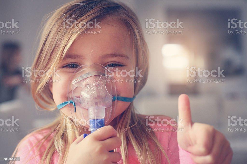 Little girl using inhaler. stock photo