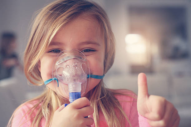 little girl using inhaler. - oxygène phénomène naturel photos et images de collection