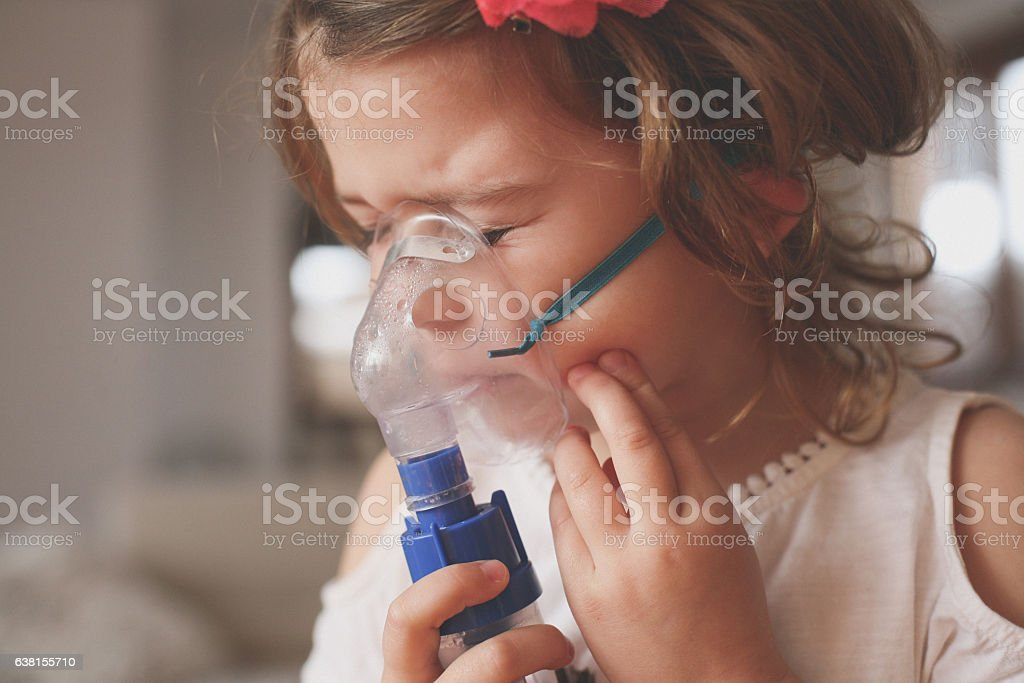 Little girl using inhaler. stock photo