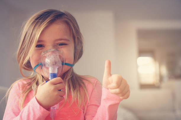 Little girl using inhaler. Little girl using inhaler and showing OK. Looking at camera. Space for copy. oxygen mask stock pictures, royalty-free photos & images