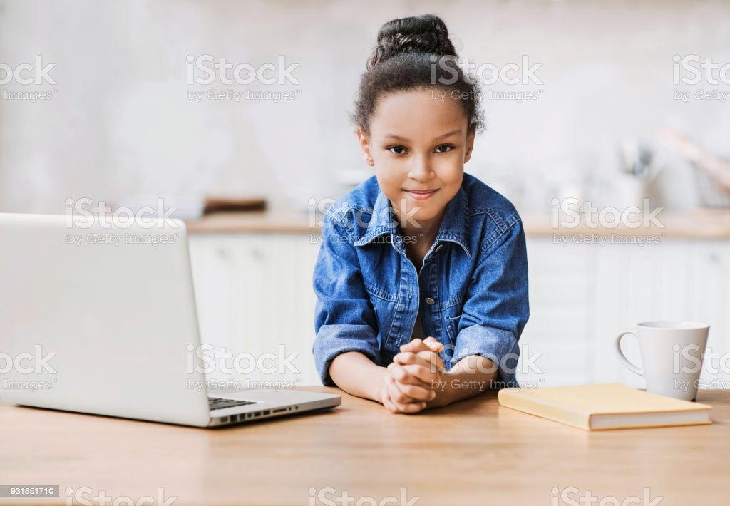 Little girl using laptop computer at home stock photo