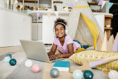 A little African American girl is on the floor in the living room, she enjoys using a laptop while listening to music
