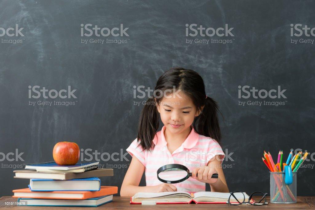 menina, usando a ferramenta Lupa lendo livro - foto de acervo