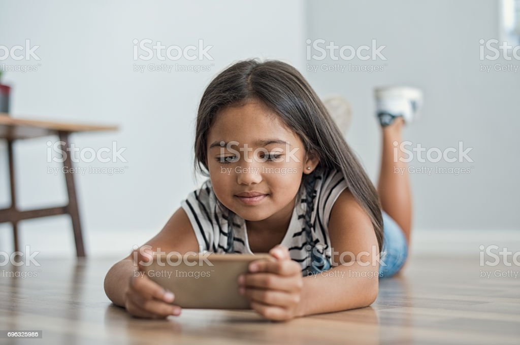 Little girl using mobile phone stock photo