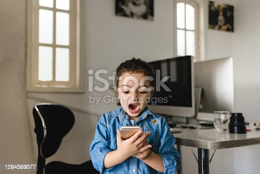 Little girl using smartphone making funny face