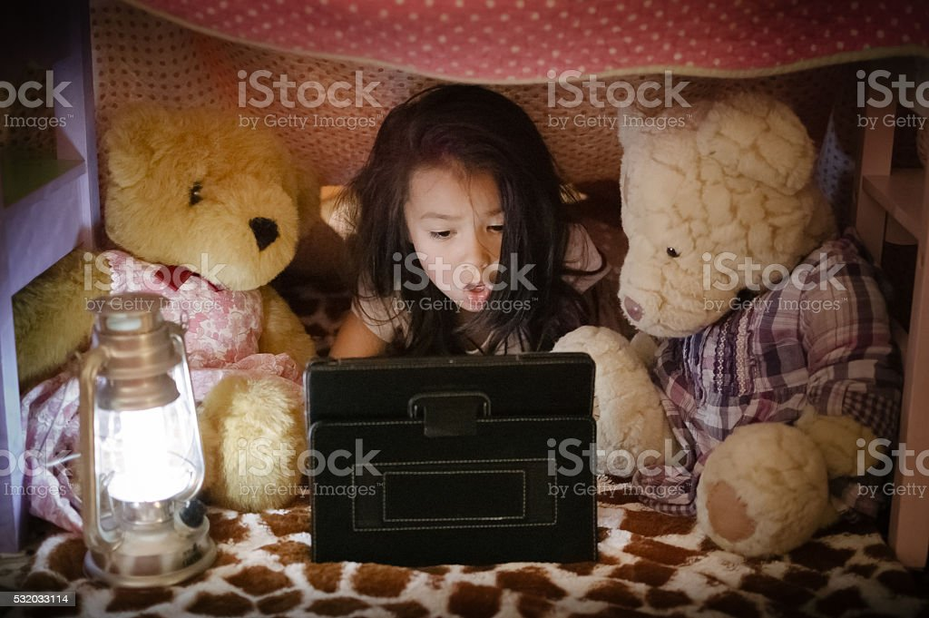 Little girl using iPad/tablet with teddy bears in fort stock photo