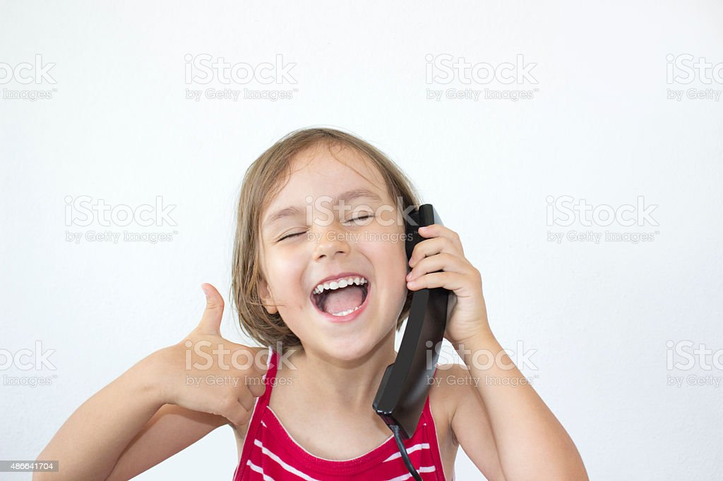 Little girl using telephone gesturing thumbs up against white ba stock photo