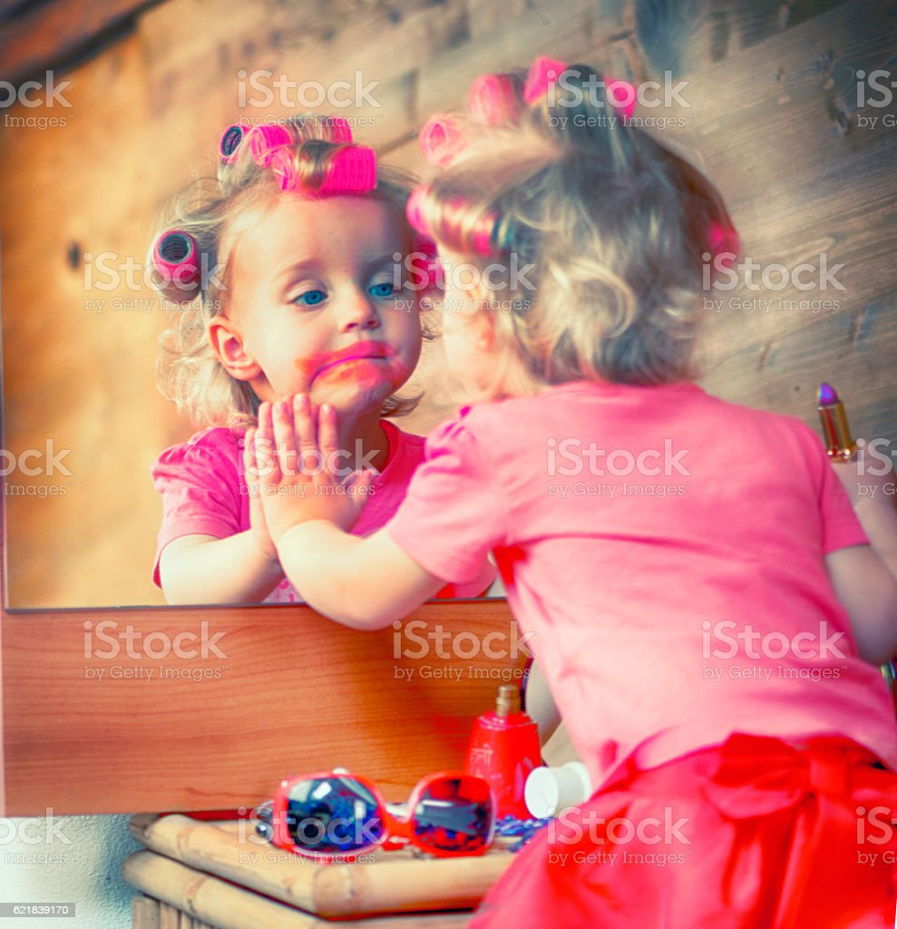 Little girl using the red lipstick stock photo