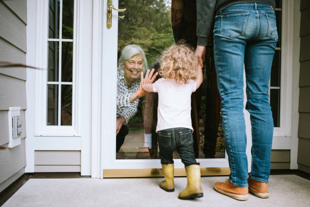 little girl visits grandparents through window - visita foto e immagini stock
