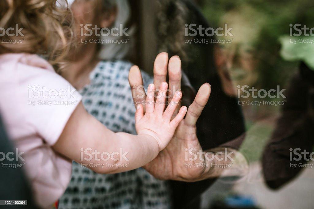 Kleines Mädchen besucht Großeltern durch Fenster - Lizenzfrei Corona-Virus Stock-Foto