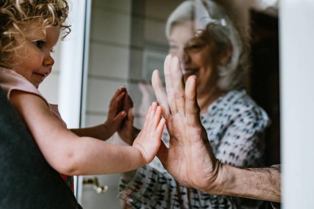 meisje bezoekt grootouders door raam - raam bezoek stockfoto's en -beelden
