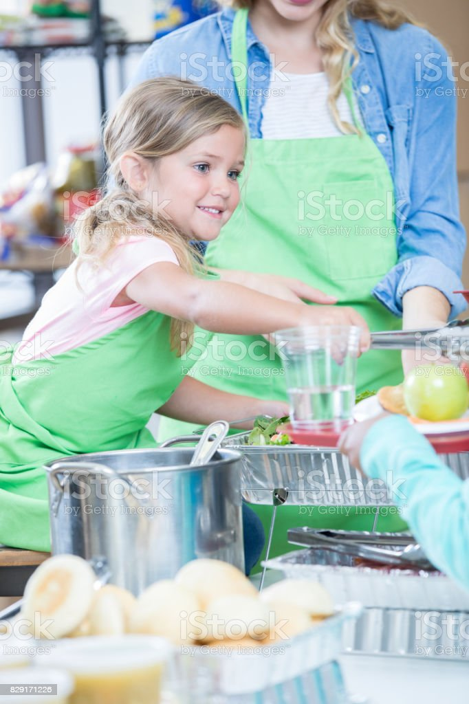 Cheerful little girl serves alongside her mom in a soup kitchen. She...