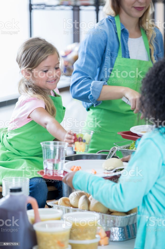 Cute little girl helps her mom serve healthy meals in soup kitchen.