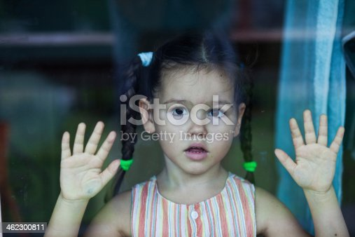 istock Little girl waiting by a window 462300811