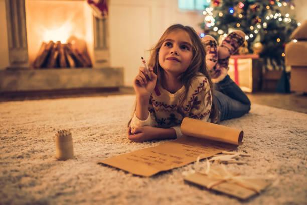 kleines mädchen wartet auf weihnachten. - weihnachts wunschliste stock-fotos und bilder