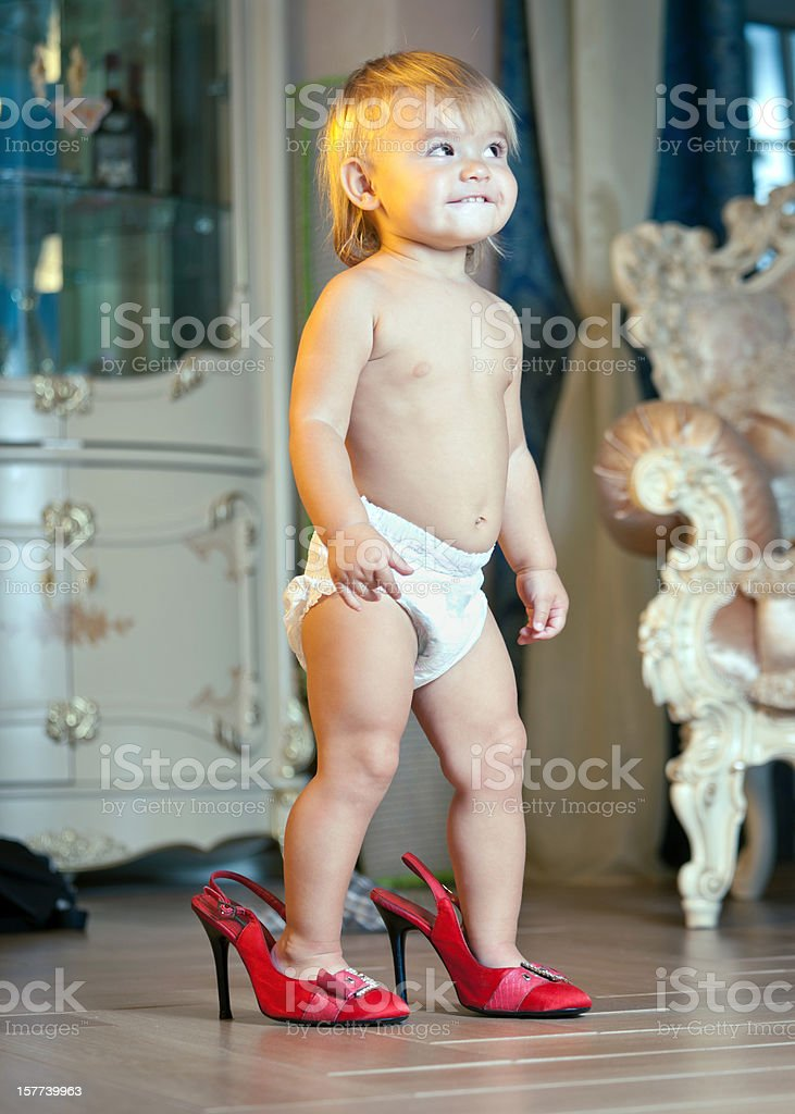 Little girl walking in red high heels shoes stock photo