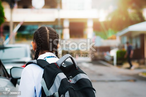 Little girl walking into school with backpack in the morning under warm sunshine. Education concept.