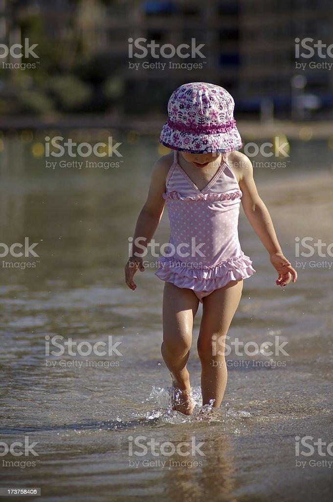 Little girl walking on a beach stock photo