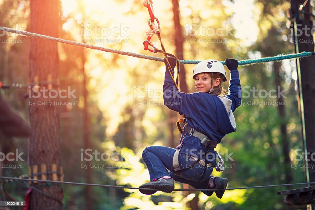 Little girl walking on line in ropes course adventure park stock photo