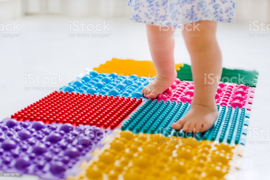 little girl walking on massage Mat stock photo