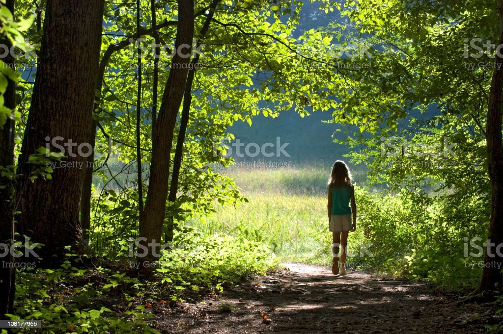 Little Girl Walking Through Edge of Forest into Field royalty-free stock photo