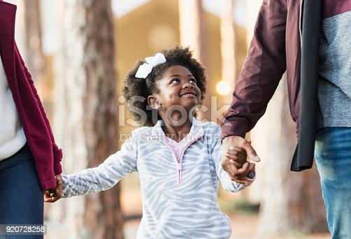 istock Little girl walking with family, looking at father 920728258