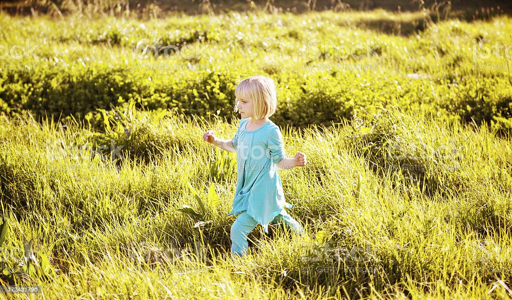 Little girl walks alone through open, grassy countryside stock photo