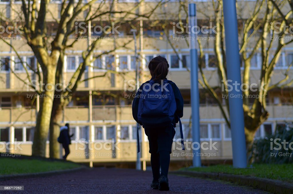 Little girl walks to school alone in the street stock photo