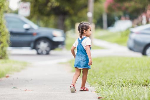 The little preschool age girl wanders alone near a busy street in her neighborhood.