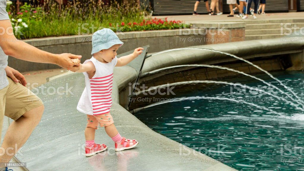 A little girl wants to swim in the fountain. Baby goes to the...