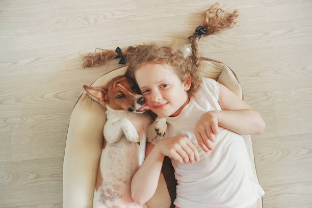 Little girl was embracing a puppy on wood background. – Foto